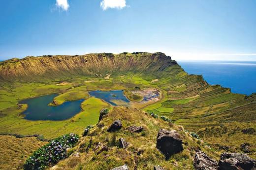 Sytě zelený kráter s jezerem.