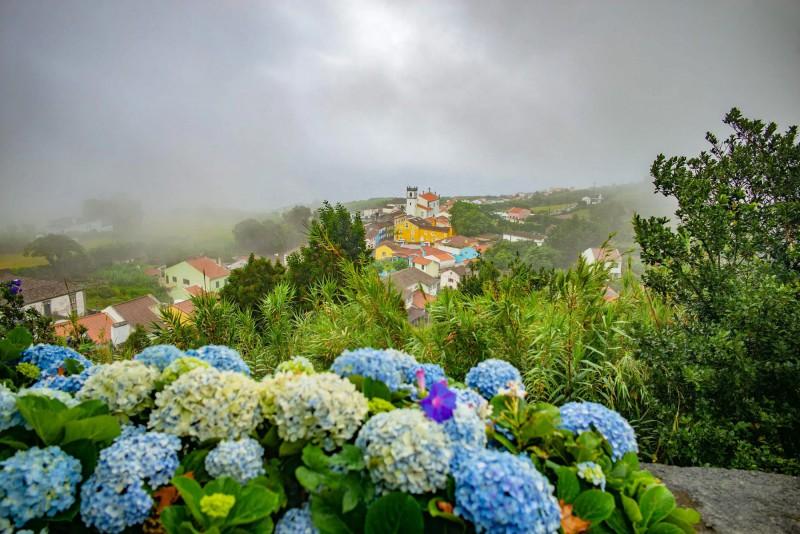 Malé barevné městečko na Azorech zahalené v mlze.