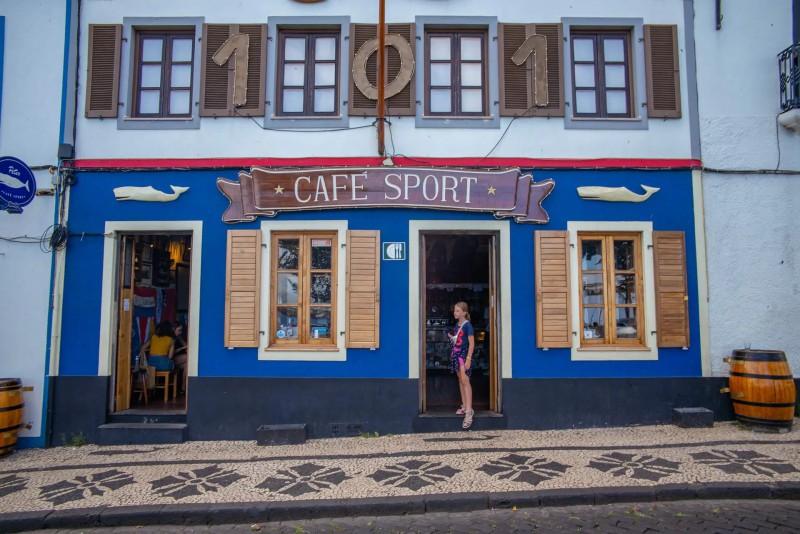 Vstup do Peters cafe sport baru z chodníku s mozaikou.