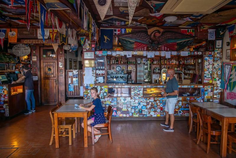 Interiér baru s vlaječkami a odznaky, které zde zanechali cestovatelé.