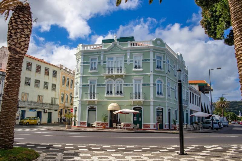 Krásná světle zelená budova s posezením.