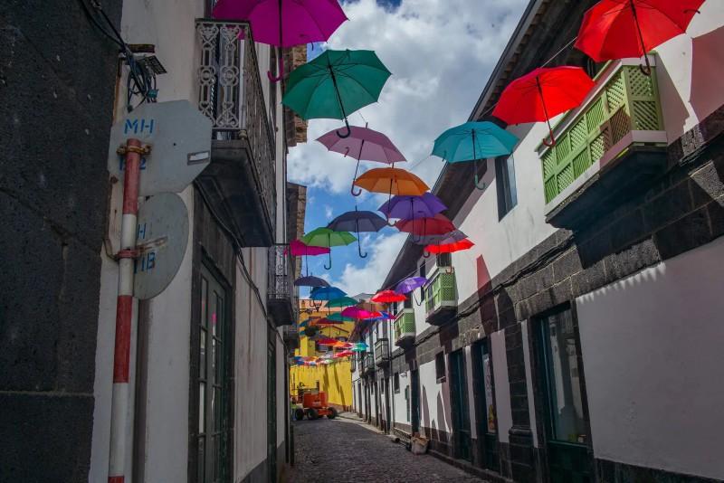 Ulička, nad kterou visí barevné deštníky.