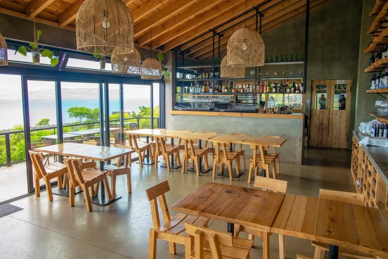 Restaurace s barem a dřevěnými stoly a židlemi.
