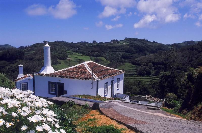 Bílý domek usazený v kopcích.