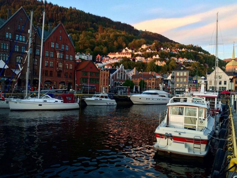 Přístav s loděmi a panorama města v kopci.