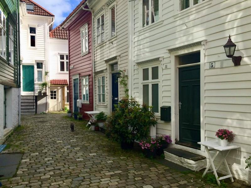 Ulička v Bergenu s bílými a červenými dřevěnými domky.