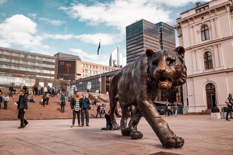 Velká bronzová socha tygra uprostřed náměstí.