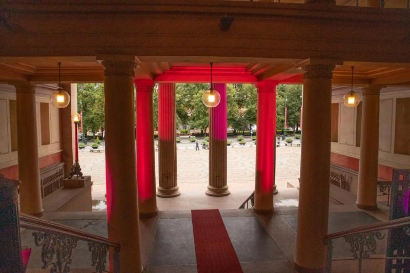 Aula s červeně podsvícenými sloupy a pohledem do zahrady.