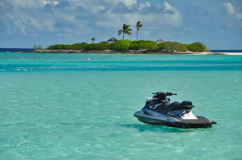 Vodní skútr na tyrkysové vodě s výhledem na ostrov.