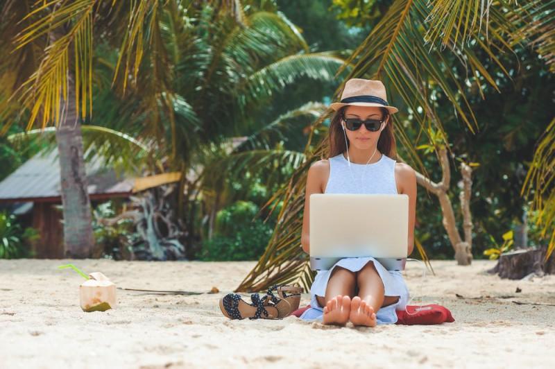 Digitální nomádka pracující na pláži