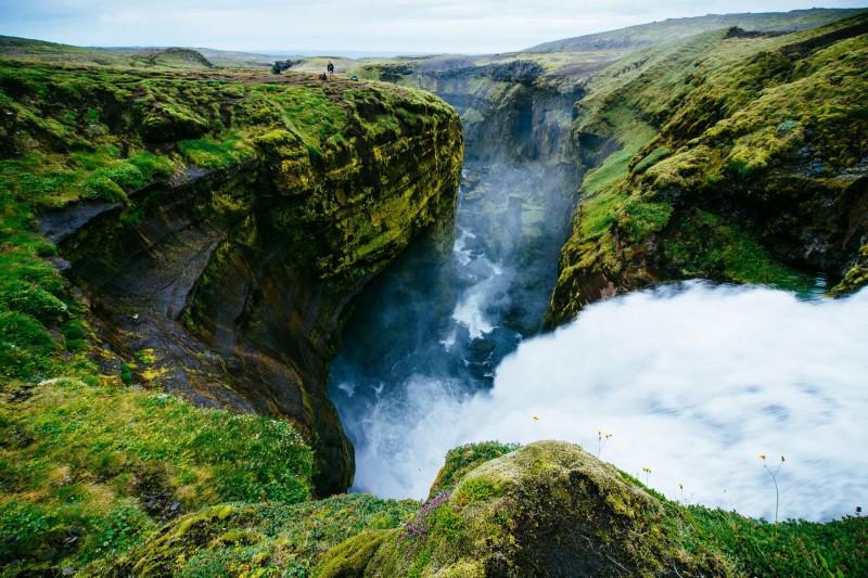 Kaňon nad vodopádem zasazeno do krásné zelené islandské přírody.