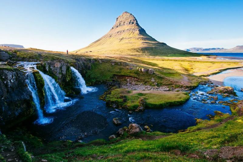 Zelená krajina s horou a klidným Kostelním vodopádem.