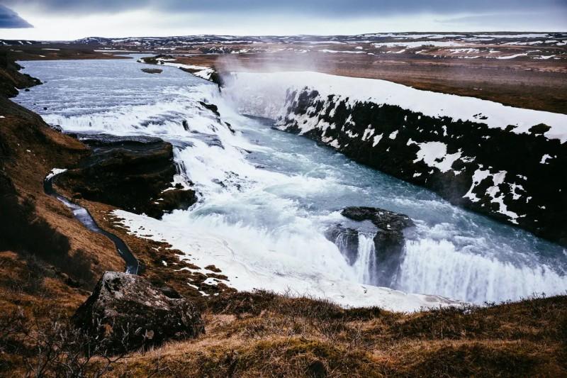 Zasněžená krajina a divoká voda vodopádu Gullfoss.