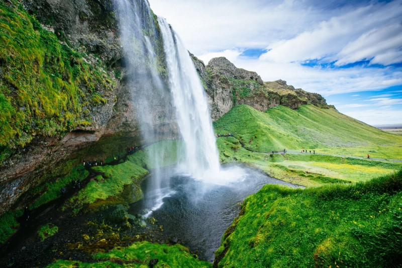 Zelené islandské kopce a cesta pod vodopádem Seljalandsfoss.