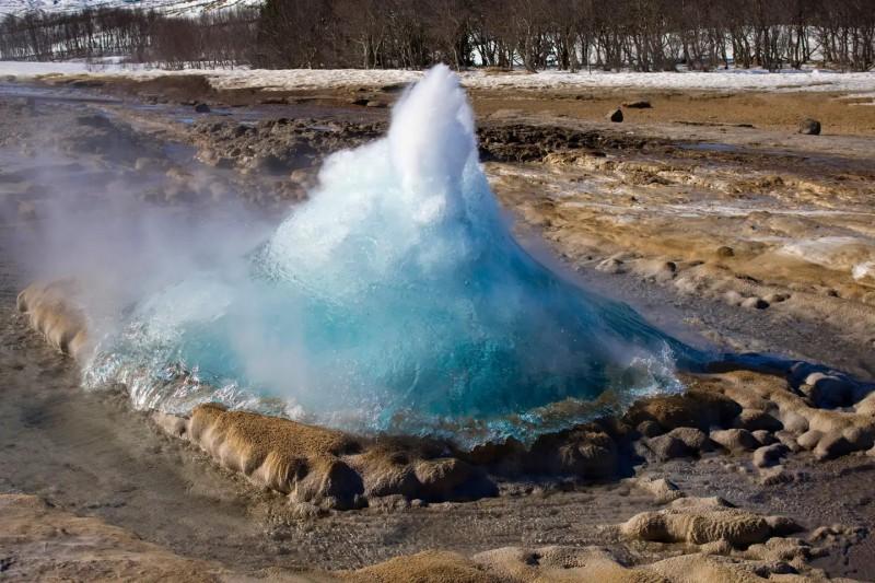 Gejzír se připravuje k výbuchu a voda se pomalu zvedá.