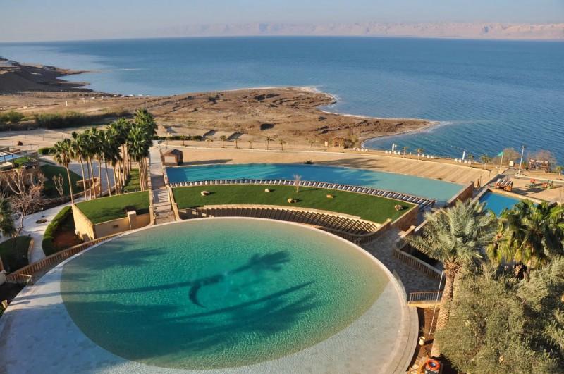 Pohled na luxusní hotelový bazén v pozadí s Mrtvým mořem.