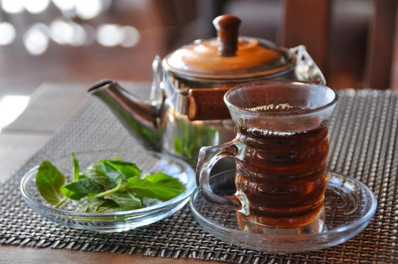 Šálek s čajem a větvičky máty.
