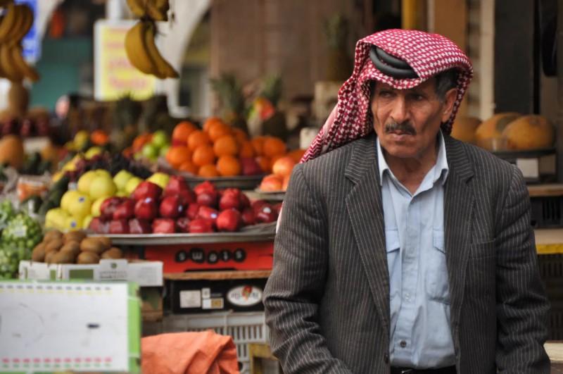 Místní prodavač na trhu s typickou pokrývkou hlavy.