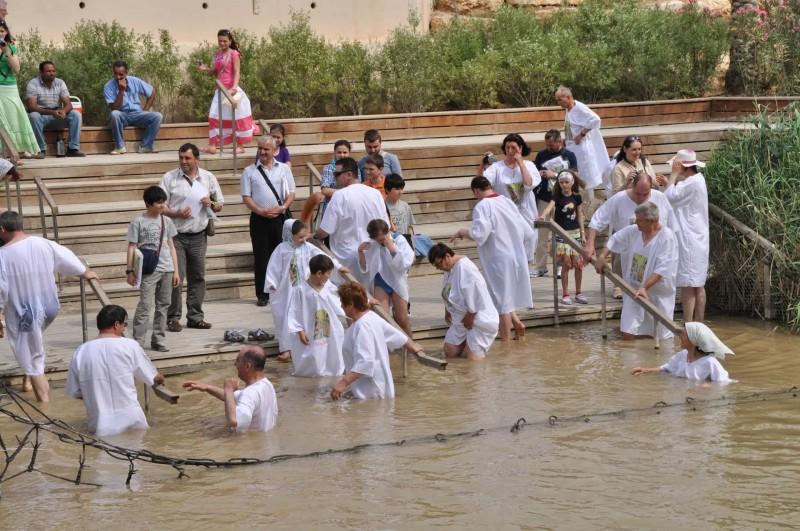 Poutníci oblečení do býlích trik, koupající se v kalné řece Jordán.