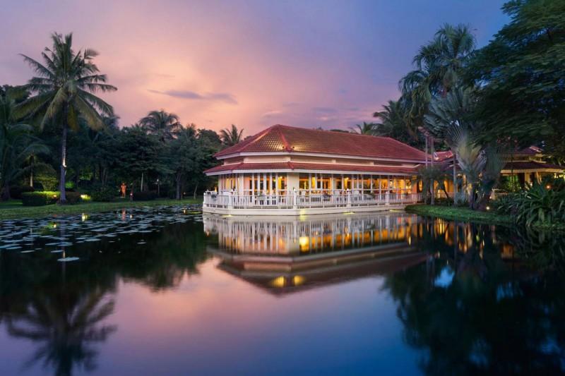 Restaurace hotelu uprostřed zahrady s jezerem.