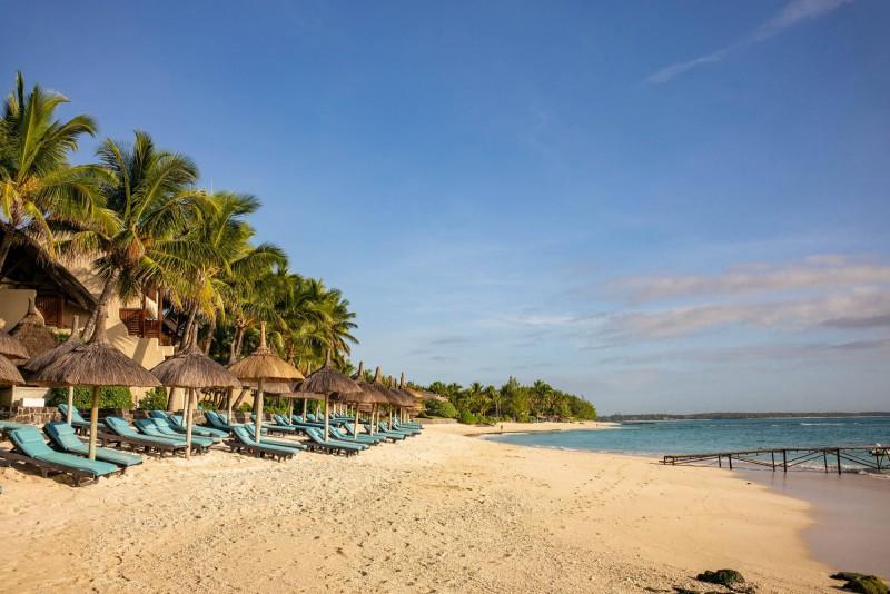 Krásná písečná pláž lemována palmami.