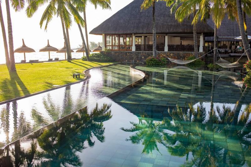 Bazén v krásné palmové zahradě, že kterého je vidět na moře.