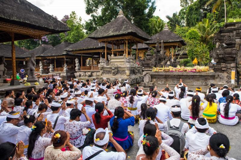 Náboženské modlitby a balijské oběti bohům v podobě misek s ovocem a květinami