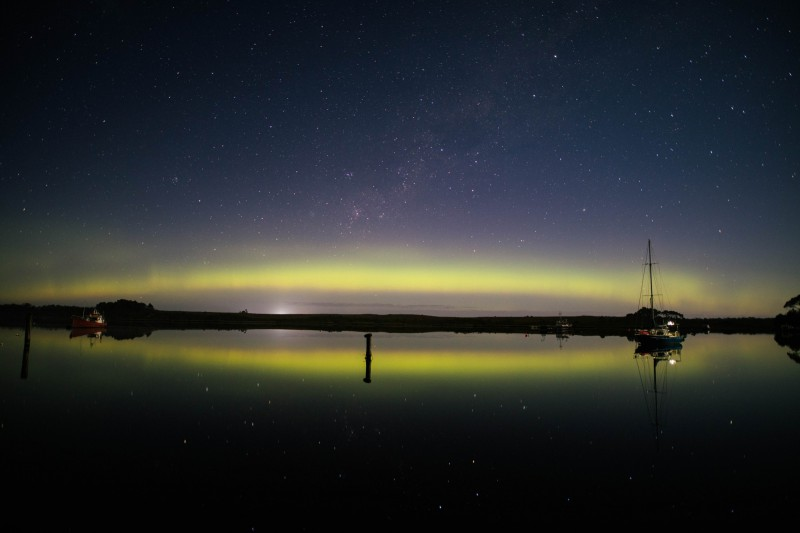 Polární záře odrážejíci se nad vodou v Strahan, Austrálie