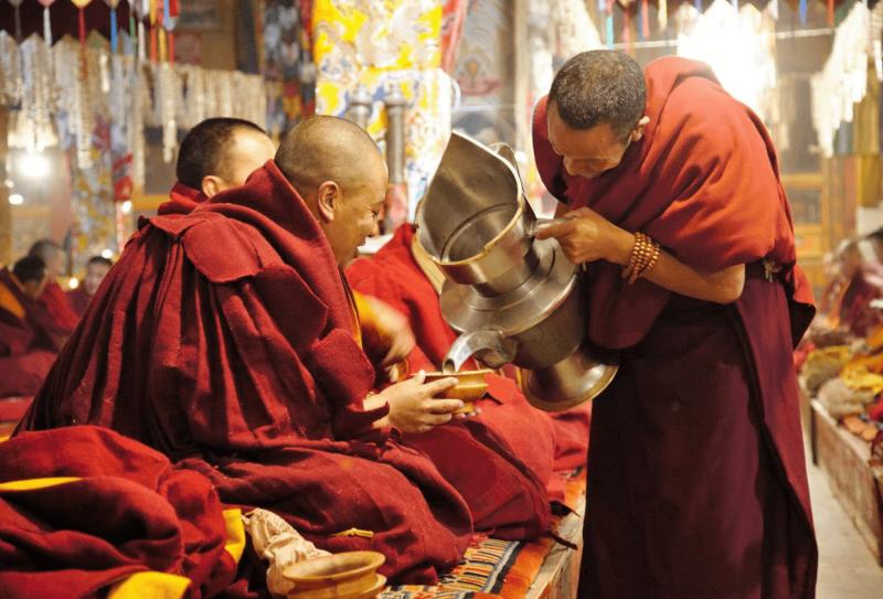 Mnich nalévá vodu ostatním mnichům v tibetských klášterech